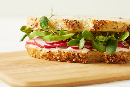 close-up shot of tasty sandwich with radish slices and pea shoots on wooden cutting board Фото со стока