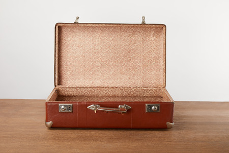 Open vintage suitcase on wooden table