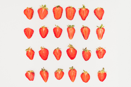 Rows of cut strawberries isolated on white background Stock Photo