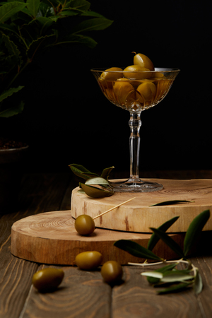 vintage glass with olives and oil on stacked boards Stock Photo
