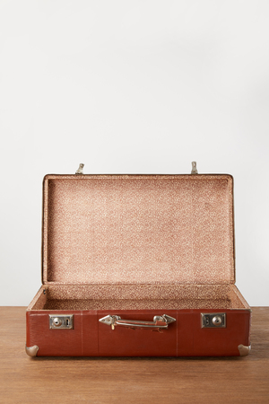 Old open brown empty suitcase on wooden table