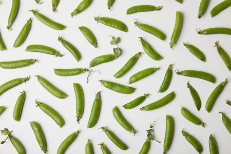 top view of ripe pea pods spilled on white surface