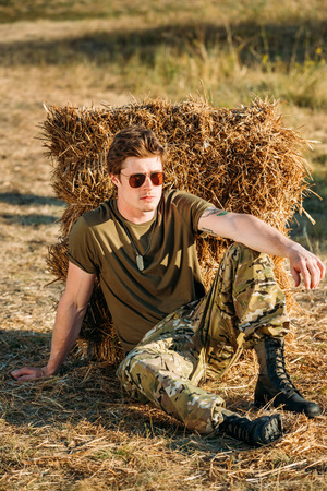 young soldier in military uniform and sunglasses resting near hay on range