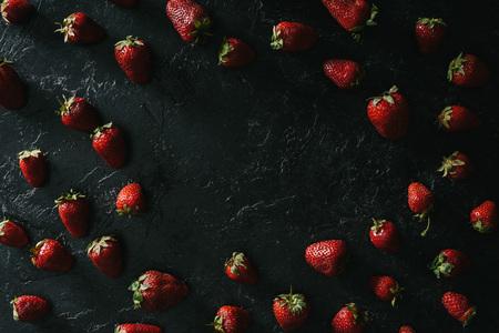 Frame of raw juicy strawberries on dark background Stock Photo