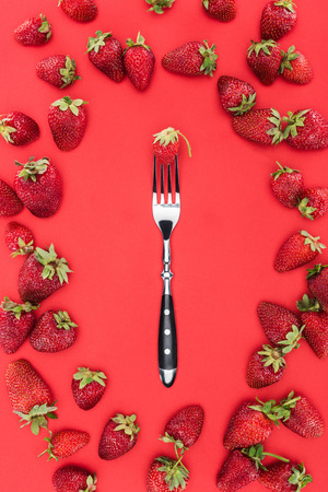 Fork in frame of strawberries isolated on red background Reklamní fotografie