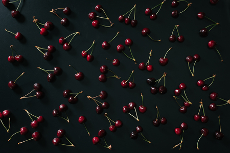 top view of red ripe sweet cherries on black background