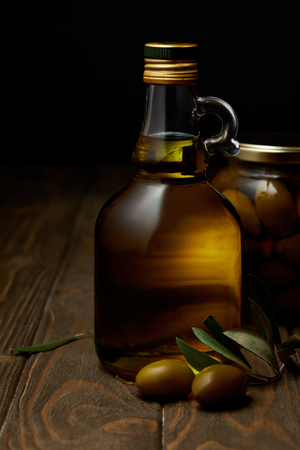 bottle of aromatic olive oil with branch and jar on wooden table Stock Photo