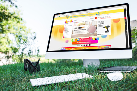 selective focus of textbook and computer with aliexpress website on grass outdoors