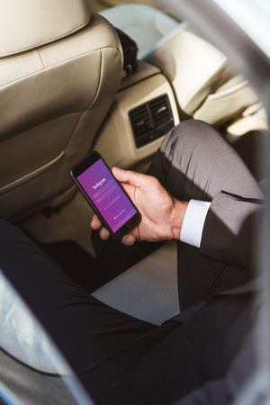 cropped image of businessman holding smartphone with loaded instagram page in car Editorial