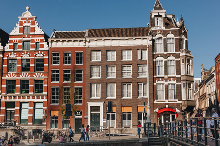 20 MAY 2018 - AMSTERDAM, NETHERLANDS: facades of old buildings on street of Amsterdam on sunny day Redactioneel