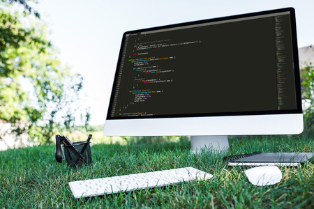 selective focus of computer with programming language code on grass outdoors