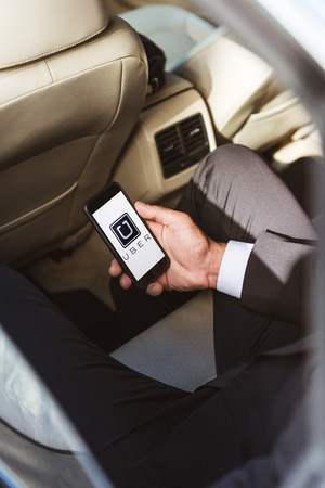 cropped image of businessman holding smartphone with loaded uber page in car Editorial
