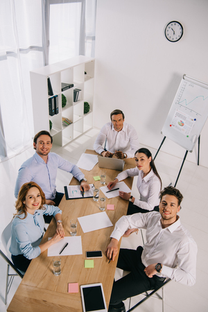 high angle view of smiling business colleagues at workplace in office