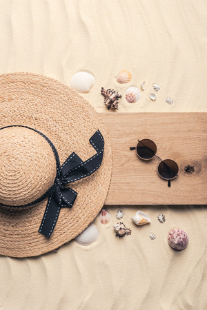 Straw hat with sunglasses on wooden pier on sandy beach