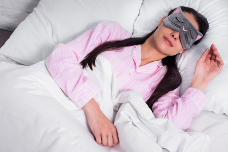 portrait of woman in pink pajamas and sleeping mask sleeping in bed at home