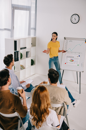 business people in casual clothing listening to female mentor at white board on business training in office Stock Photo