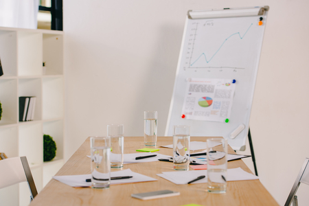 close up view of white board with graphic, papers and glasses of water on table in office Stock Photo