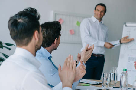 selective focus of colleagues applauding to mentor during business training in office