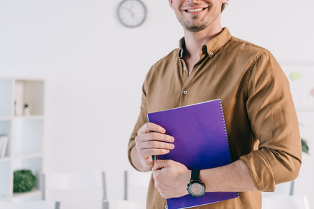 cropped shot of smiling businessman in casual clothing with notebook in office, business training concept