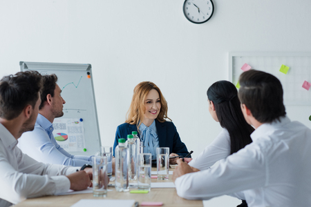 partial view of business colleagues having discussion at workplace in office Stock Photo