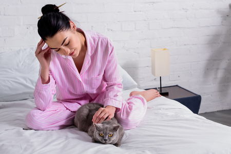 woman in pajamas with britain shorthair cat resting on bed at home Standard-Bild - 106365114