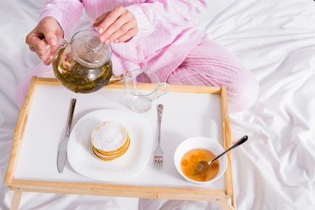 partial view of woman in pink pajamas pouring green tea into cup while having breakfast in bed at home
