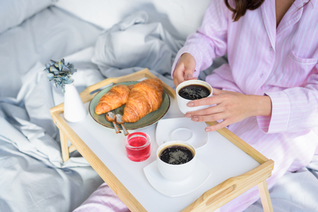 cropped view of woman in pink pajamas having breakfast in bed
