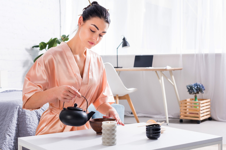 attractive woman in silk bathrobe making tea while having tea ceremony in morning at home Imagens