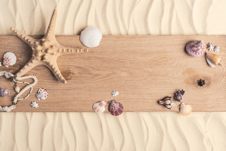 Summer travel template with seashells on wooden pier on light sand
