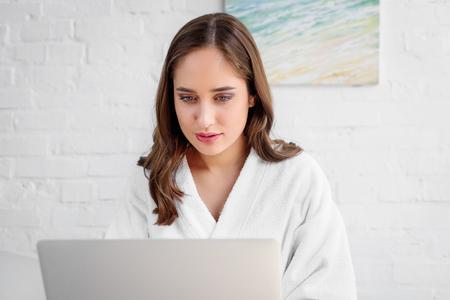 beautiful woman in bathrobe using laptop at home