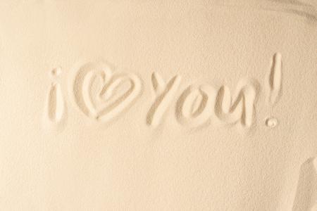 I love you inscription on light sand texture
