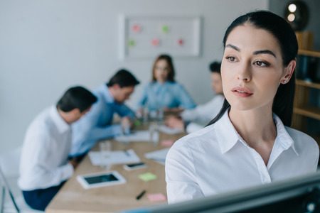 selective focus of pensive businesswoman and colleagues behind at workplace in office