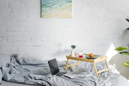 laptop and breakfast with croissant and coffee on tray in bedroom with painting on wall Stock Photo