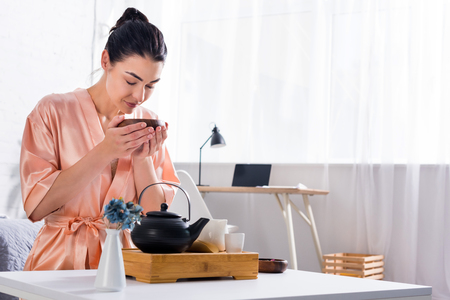 woman in silk bathrobe with wooden bowl in hands having tea ceremony in morning at home Imagens