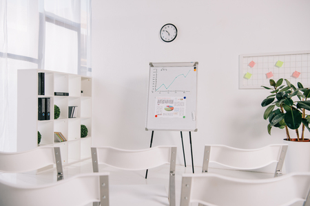 white empty chairs and white board with graphic in office, business training concept Stock Photo