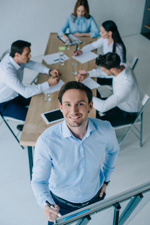 selective focus of smiling businessman at white board and coworkers at workplace in office 版權商用圖片