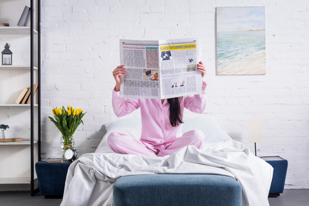 obscured view of woman in pajamas with newspaper in bed at home Stock Photo