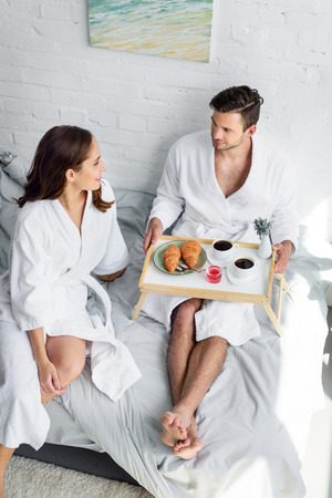 young couple having breakfast on tray in bed