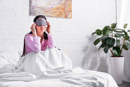 woman in pink pajamas and sleeping mask sitting on bed at home