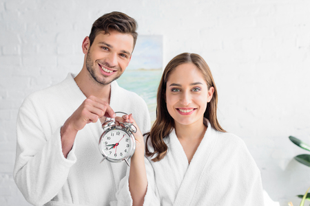 smiling couple in white bathrobes holding alarm clock and standing in bedroom in morning 版權商用圖片