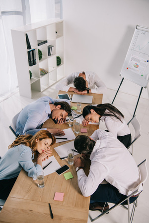 high angle view of tired business colleagues sleeping at workplace in office