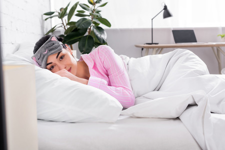 portrait of woman in pink pajamas and sleeping mask lying in bed at home Banco de Imagens