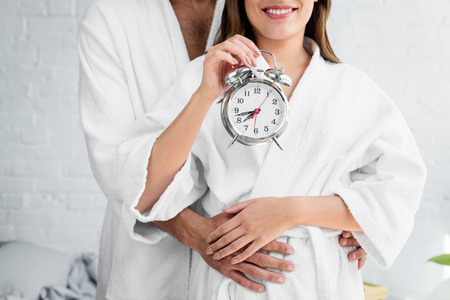 cropped view of couple in white bathrobes holding alarm clock and standing in bedroom 스톡 콘텐츠