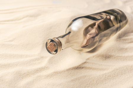 Corked bottle with message on sandy beach