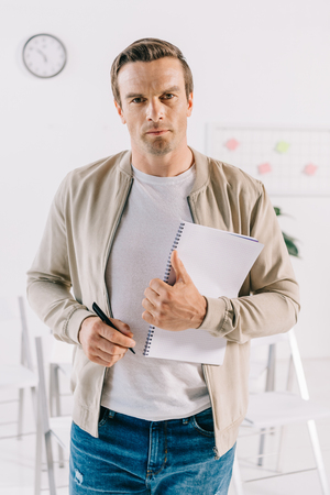portrait of businessman in casual clothing with notebook looking at camera in office, business training concept