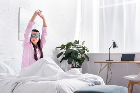 portrait of woman in pink pajamas and sleeping mask stretching in bed in morning