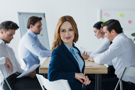 selective focus of smiling businesswoman and colleagues at workplace in office Stock Photo