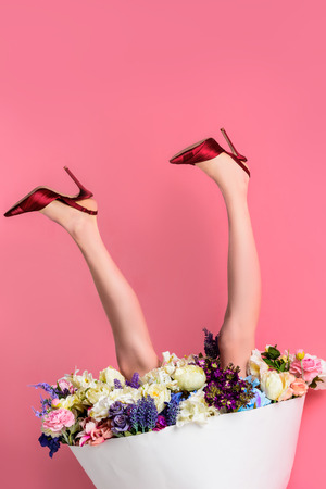 cropped shot of girl in high heeled shoes and skirt with beautiful flowers on pink, upside down view Stock Photo