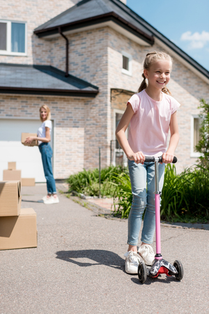 smiling little child riding on kick scooter while her mother unpacking cardboard boxes in front of new house Banco de Imagens