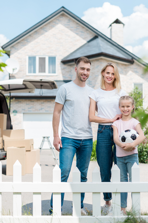 front view of happy family with little daughter holding soccer ball in front of new house